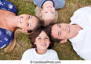 Cheerful family lying in circle on the grass in a park