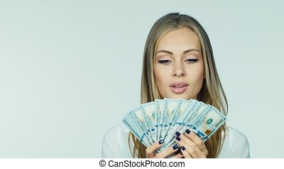 An attractive woman with a fan of dollars