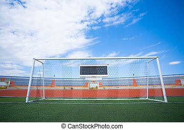 STADIUM - Football field with goal and tablo on blue sky -...