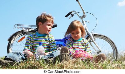 boy and girl sits on field near bicycle and eat