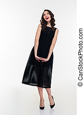 Joyful inspired retro styled woman in black dress and shoes...