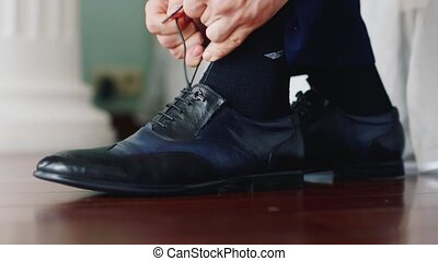 Hands of man tied to the shoe lace