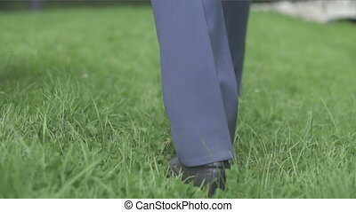 man in black shoes walking on the lawn