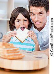 Cute little boy and his father eating bread in the kitchen