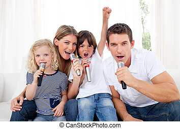 Portrait of a lively family singing through microphone in...