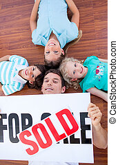 Happy family lying on floor after buying a house