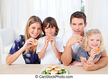Smiling family eating burgers in the living room at home