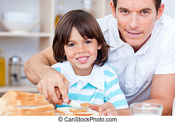 Portrait of a father and his son spreading jam on bread in...