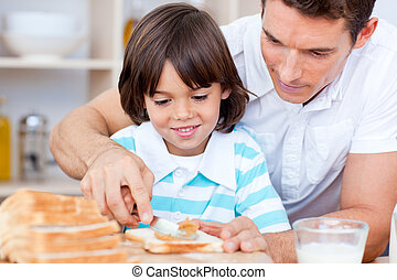 Loving father and his son spreading jam on bread in the...