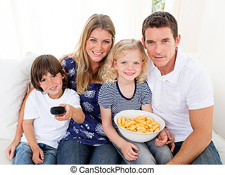 Loving family watching television sitting on sofa at home