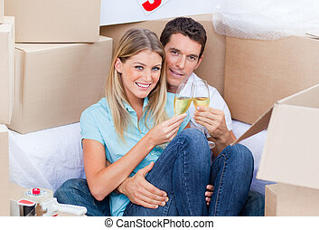 Cheerful couple toasting with Champagne after move in
