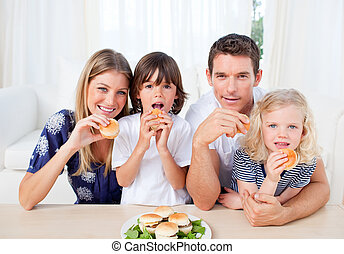 Positive family eating burgers in the kitchen
