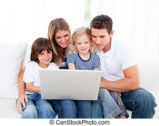 Cheerful family using a laptop sitting on sofa at home