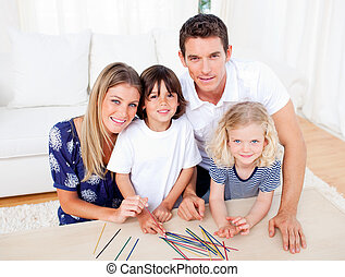 Cheerful family playing mikado in the living room at home
