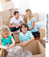 Cheerful family packing boxes while moving house