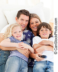 Caucasian family watching television sitting on sofa at home