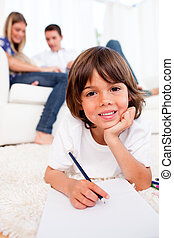 Smiling little boy drawing lying on floor in the living room
