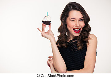 Retro styled woman holding birthday cupcake with candle and...