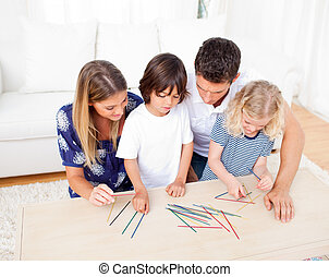 Loving family playing mikado in the living room at home