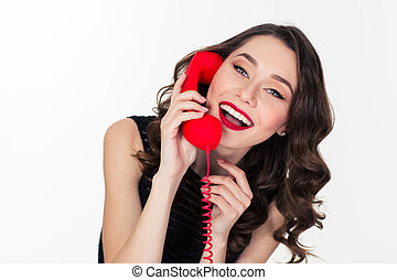 Cheerful attractive curly retro styled woman talking on red...