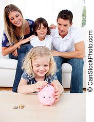 Smiling little girl inserting coin in a piggybank in the...
