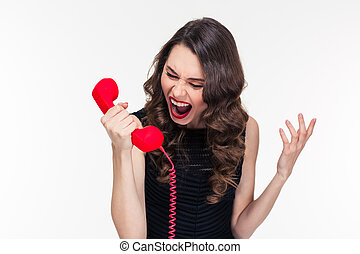 Crazy raged retro styled female shouting in red telephone...