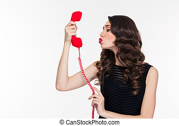 Cute woman in retro style sending kiss into telephone...