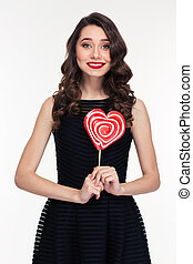 Beautiful happy curly retro styled woman holding heart...