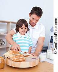 Charming father and his son spreading jam on bread in the...