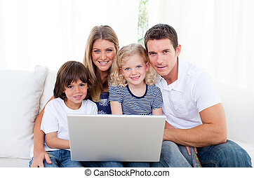 Portrait of a joyful family using a laptop sitting on sofa