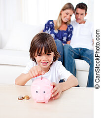 Joyful little boy inserting coin in a piggybank in the...