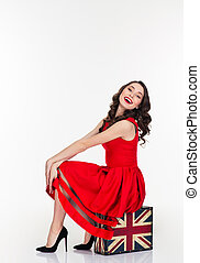 Cute lovely woman sitting on vintage suitcase with british...