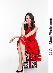 Happy attractive woman in red dress sitting on vintage...