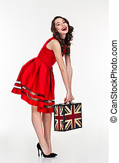 Cheerful attractive curly woman holding vintage suitcase...