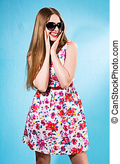 Portrait of beautiful cheerful girl in a summer dress with her hands on the cheeks