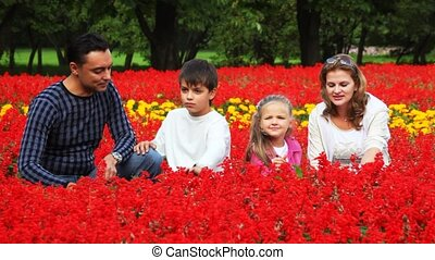 Family with boy and girl iron and smell flowers