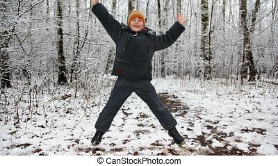 Happy boy dances against winter wood, time lapse, boy around...
