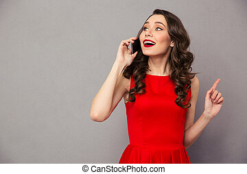 Happy woman in red dress talking on the phone - Portrait of...