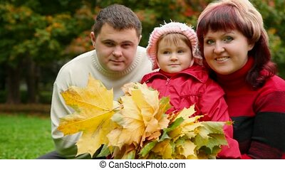 family of three person with autumn leafs in park