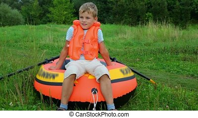 boy dressed in life jacket dragging inflatable rubber