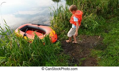 boy puts on a life jacket sitting down to inflatable rubber
