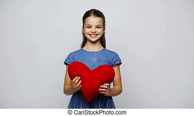 happy smiling girl with red heart shaped pillow - love,...