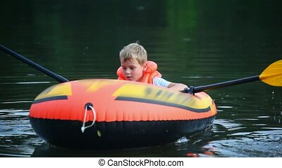 boy turn round on an inflatable boat on water