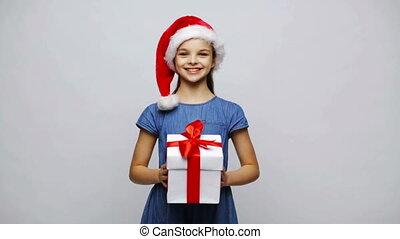 happy smiling girl in santa hat holding gift box