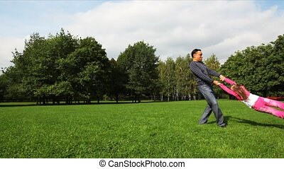 man turns girl on field in park