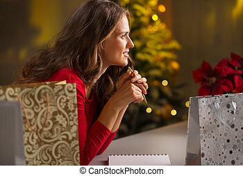 Woman among Christmas shopping bags thinking what's left to...