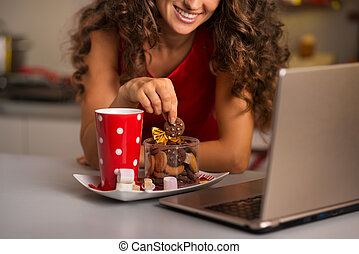 Woman having cup of hot chocolate with cookies and using...