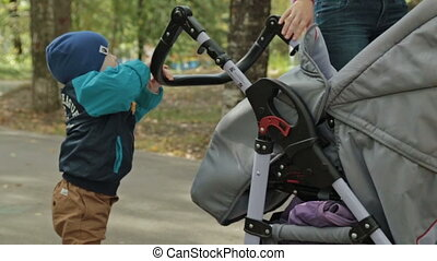 Small child toddler boy pushing a carriage in the park, HD