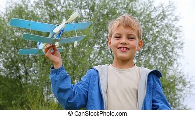 boy flying toy aircraft and running behind him