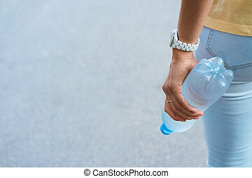 Female hand holding a plastic water bottle